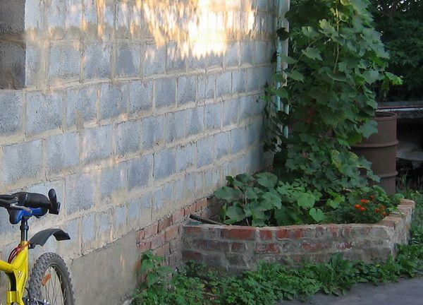 Приподнятая клумба у стены гаража