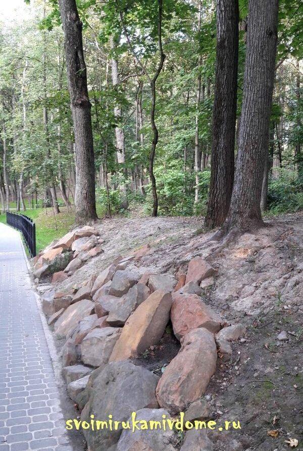 Склон возле дорожки выложен камнями в парке