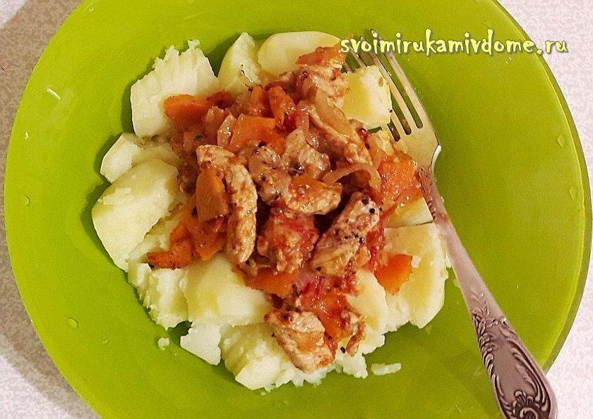 Тушёное мясо с луком, морковью, помидорами в тарелке