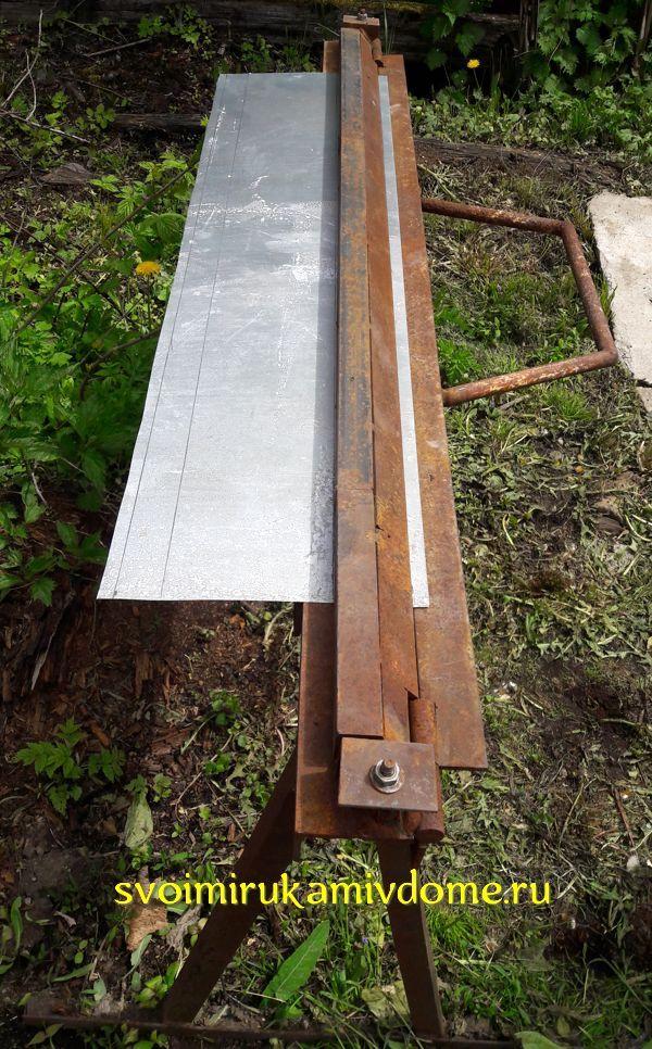 Лист металла вставлен в станок для гибки отливов